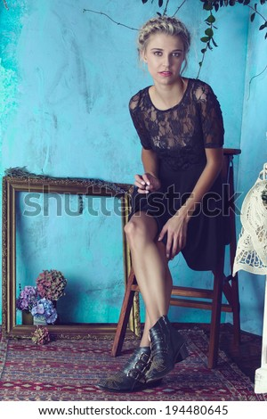 Beautiful blond woman with braid hairstyle and natural makeup. Wearing lace black dress and boots. Against grunge blue background - stock photo