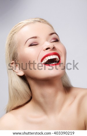 Beautiful blond woman with bright make-up. Sexy look with clean skin and red lips makeup. Laughing girl with perfect beautiful smile. Whitening teeth   - stock photo