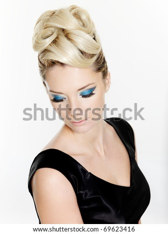 Beautiful blond woman with curly hairstyle and blue make-up of eyes - isolated on white background - stock photo