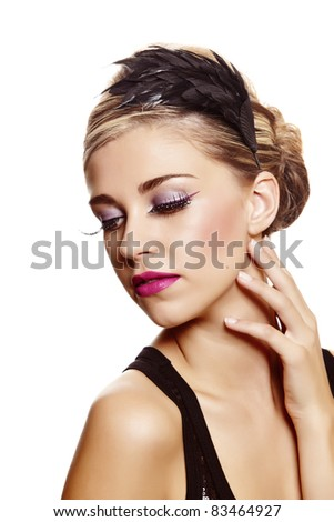 Beautiful blond woman with fashion make-up wearing hair in a classic french roll updo hairstyle with feather band over white studio background . - stock photo