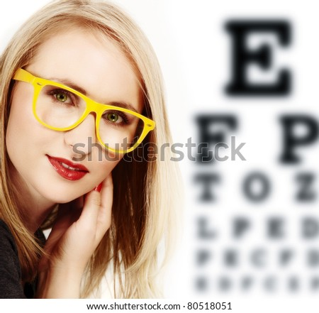 beautiful blond woman with geek yellow glasses and optometry check-up chart. - stock photo