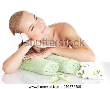 Beautiful blond woman with gentle orchid flower in hair isolated on white background, enjoying day spa, relaxing on massage table, medical beauty treatment, well being lifestyle - stock photo