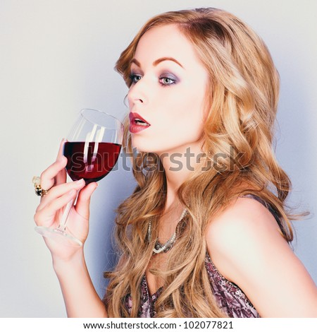 Beautiful blond woman with glass red wine