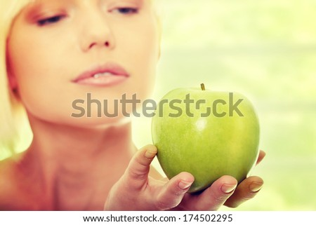Beautiful blond woman with green apple - stock photo