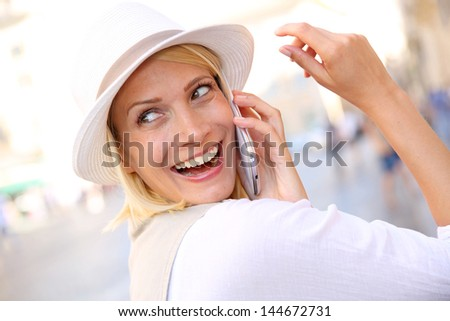 Beautiful blond woman with hat talking on the phone - stock photo