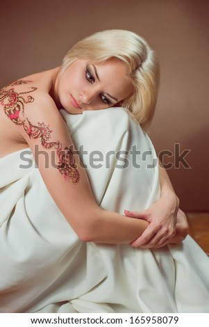 Beautiful blond woman with henna tattoo on her back.