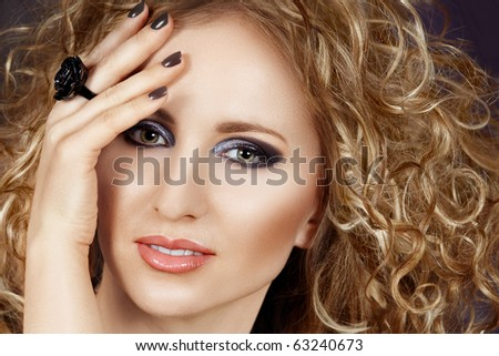 beautiful blond woman with long curly hair and smoky eyeshadow wearing grey manicure - stock photo