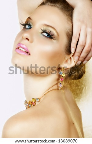 Beautiful blond woman with long lashes and colourful stones necklace and earrings and seductive smile ? not isolated - stock photo