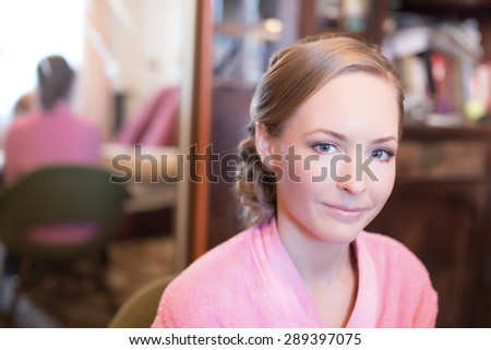 beautiful blond woman with smooth hair wearing a pink fluffy bathrobe is reflected in the mirror Preparing for the holiday or wedding
