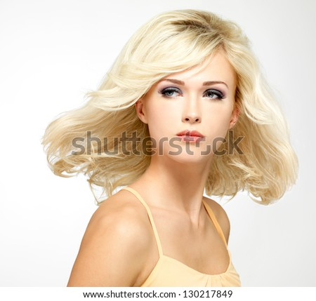 Beautiful blond woman with style hairstyle poses at studio - stock photo