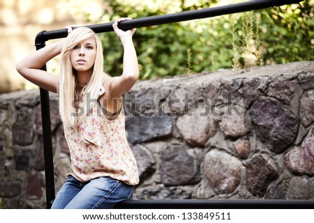 Beautiful blond young girl leaning on the wall - stock photo