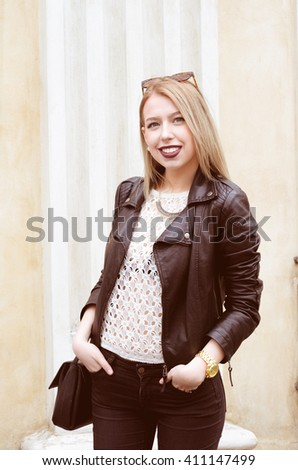 Beautiful blond young hipster girl with red lipstick and bright makeup on a sunny day outdoors. Smiling sexy woman dressed in a black leather jacket posing near old buildings