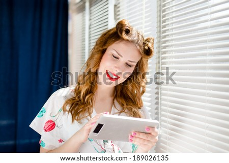 Beautiful blond young pinup woman reading on tablet pc computer and happy smiling at home by window blinds portrait - stock photo