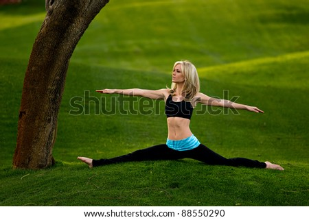 Beautiful blond young woman doing the splits with arms out in the park on a green lawn. - stock photo