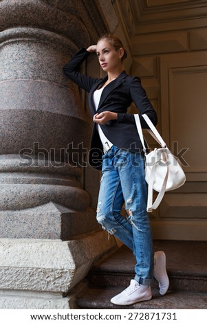 Beautiful blond young woman dressed in a coat walking down the street of the old town center.  - stock photo