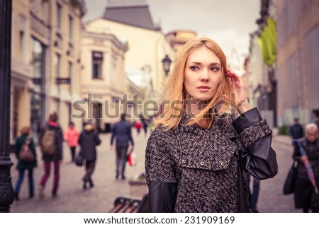 Beautiful blond young woman dressed in a coat walking down the street of the old town center. Image is colored  toned - stock photo