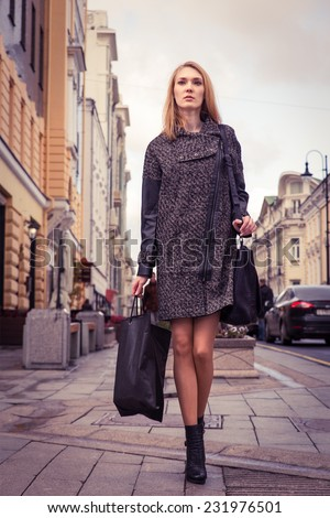 Beautiful blond young woman dressed in a coat walking down the street of the old town center. Image is colored  toned
