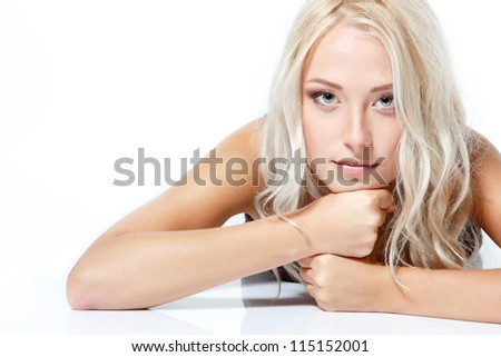 Beautiful blond young woman lying and looking at camera. Isolated on white background