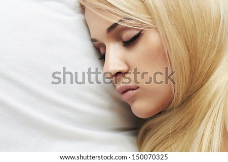 Beautiful blond young woman sleeping on the bed. beauty woman. white pillow. sweet dreams - stock photo