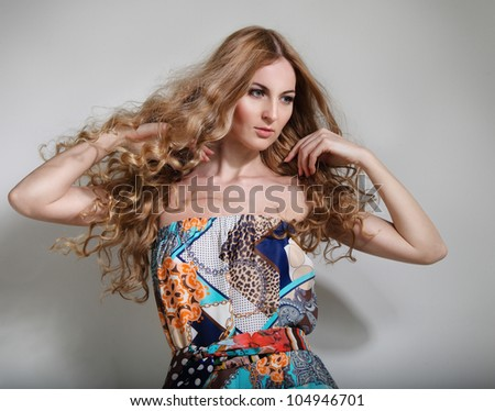 Beautiful blond young woman with long hair in colorful dress