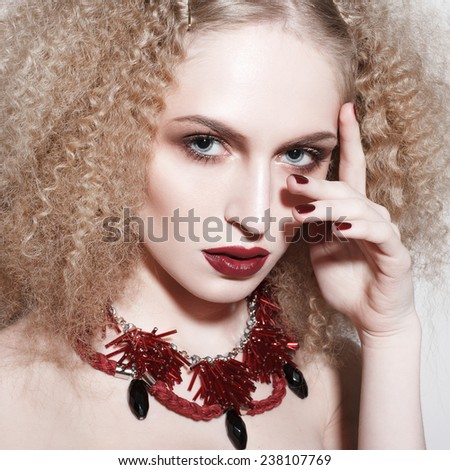 beautiful blond young woman with red lips and big interesting necklace. Evening make-up. Marsala color makeup - stock photo