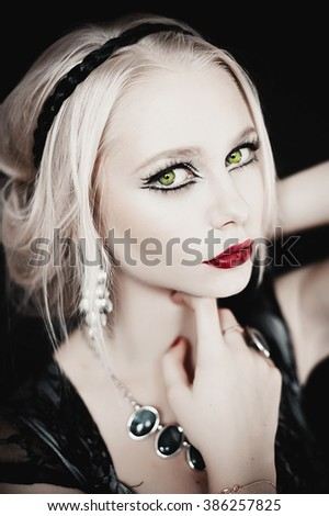 beautiful blond young woman with red lips and earrings. Evening make-up