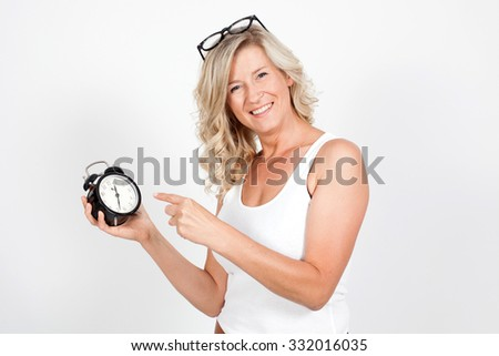 Beautiful blonde adult woman holding a clock, alarm clock. time, haste, punctuality, I'm late. It's already time. - stock photo