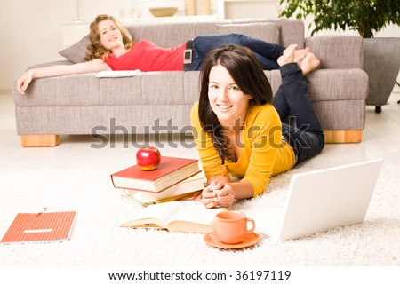 Beautiful blonde and brown teenager girls at home, learn - stock photo