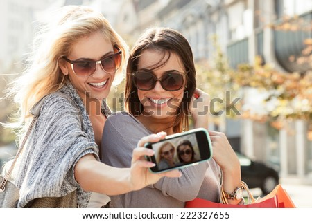 Beautiful blonde and brunette taking a selfie - stock photo