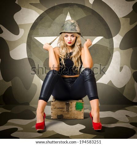 Beautiful blonde army pinup woman sitting on military ammunition crate wearing helmet and red heels. Fashion recruit - stock photo