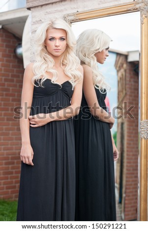 Beautiful blonde. Attractive young blond hair woman in black dress standing near the mirror and looking at camera - stock photo