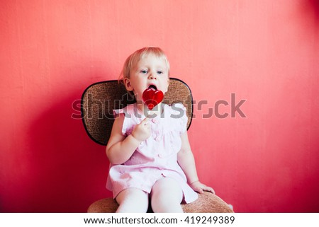 Beautiful blonde baby girl in pink with lollipop - stock photo
