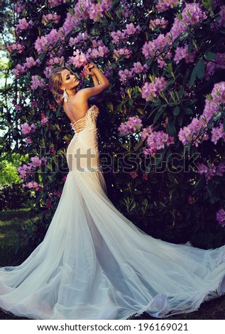 beautiful blonde bride in a luxurious wedding dress in garden with beautiful blossom - stock photo