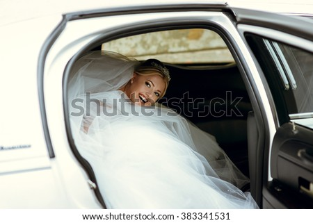 Beautiful blonde bride in the car on the wedding day - stock photo
