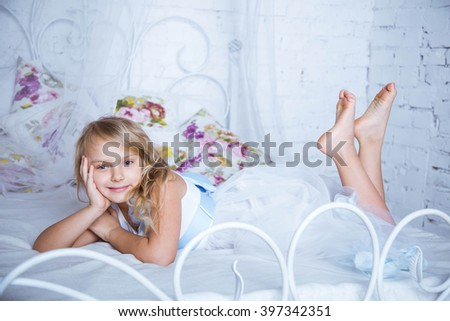 Beautiful blonde caucasian girl lies on the big white bed in a white dress.  Girl smiling and looking in camera - stock photo