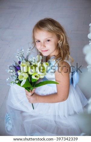 Beautiful blonde caucasian girl sitting with a bouquet of spring flowers in a white dress.  Girl smiling and looking at bouquet - stock photo
