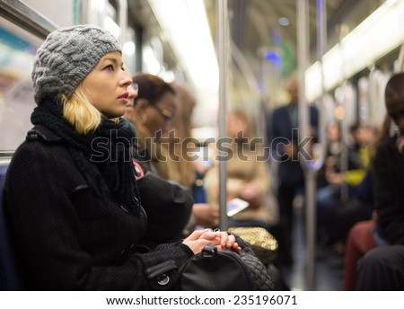 Beautiful blonde caucasian lady wearing winter coat traveling by metro in rush hour. Public transport. - stock photo