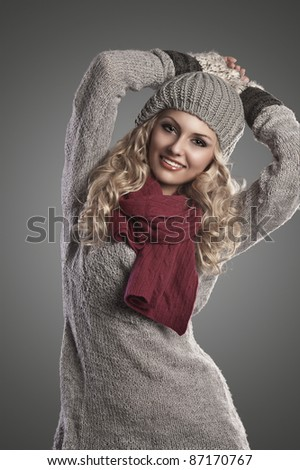beautiful blonde curly girl in a winter fashion portrait wearing grey wool and a red scarf - stock photo