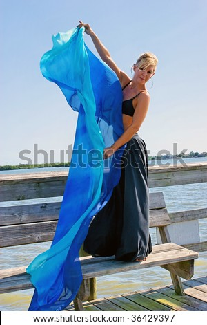 beautiful blonde dancer is standing on wooden dock bench, looking at viewer and holding a big blue silk cloth, cloth can be used as copy or text area - stock photo