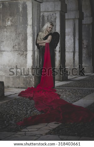 Beautiful blonde dressed in black dress and huge red cloth, in the arches of a palace in Spain - stock photo