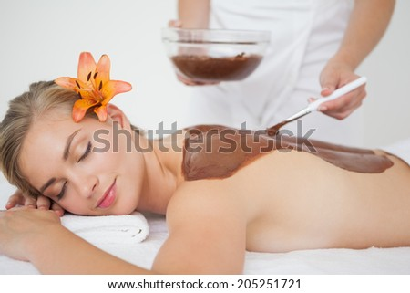 Beautiful blonde enjoying a chocolate beauty treatment at the health spa - stock photo