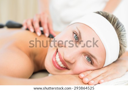 Beautiful blonde enjoying a hot stone massage at the health spa