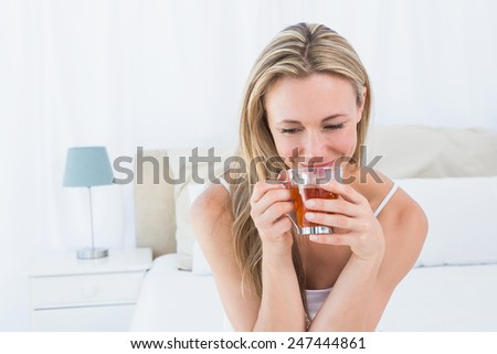 Beautiful blonde enjoying hot beverage at home in the bedroom - stock photo