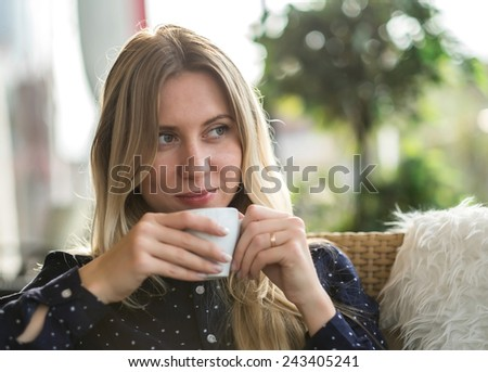 Beautiful blonde female drink coffee under sunlight - stock photo
