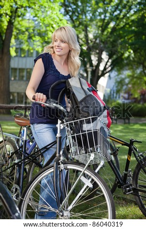 Beautiful blonde female student standing with her bike and looking away - stock photo