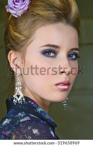 Beautiful Blonde Female With Purple Rose in Her Hair - stock photo