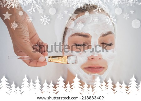 Beautiful blonde getting a facial treatment against fir tree forest and snowflakes - stock photo