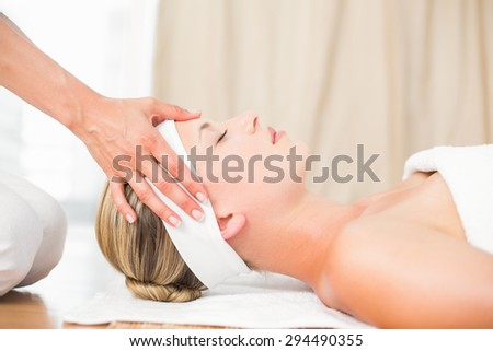 Beautiful blonde getting a head massage at health spa - stock photo