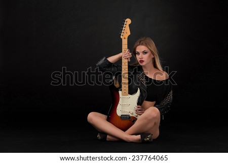 Beautiful blonde girl and guitar in rock style on a black background - stock photo