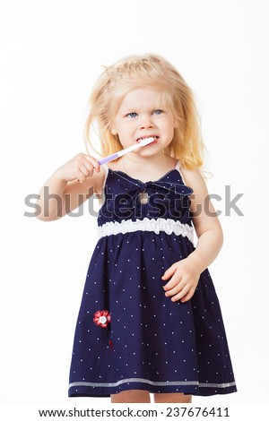 Beautiful blonde girl brushes her teeth on white background - stock photo